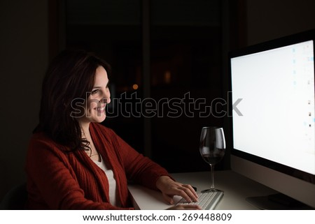 Young woman using her computer at night - stock photo