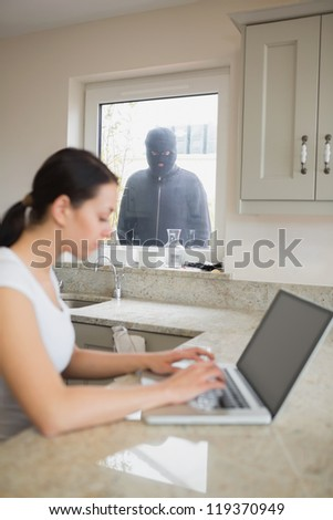 Young woman using her laptop and is observed by a robber at the window - stock photo