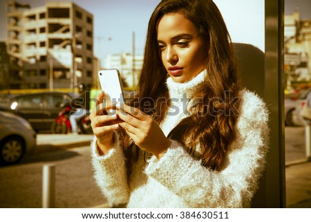 Young woman using her mobile phone on the street. Outdoors shot, horizontal. - stock photo