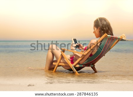 Young woman using her smart phone at the beach - stock photo
