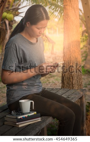 Young woman using her smartphone seriously while sitting in outdoor park on wood table in morning time on weekend. Freelance business working and phone addiction concept - stock photo