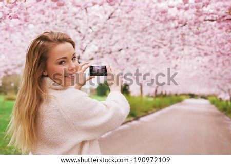 Young woman using her smartphone to capture images of the path and cherry blossoms tree at park, Young female looking over her shoulder while taking pictures with her phone at spring blossom garden. - stock photo