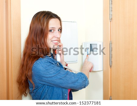 Young woman using house videophone  - stock photo