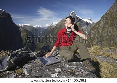 Young woman using laptop and walkie talkie on boulder against mountains - stock photo