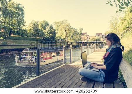 Young woman using laptop at a riverbank. - stock photo