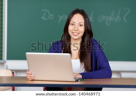 young woman using laptop at english lesson in class room - stock photo