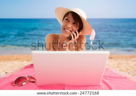 Young woman using laptop at the beach, working and mobile speaking - stock photo