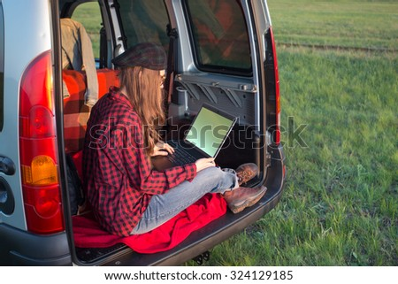 Young woman using laptop computer sitting in car relaxing and enjoying her trip. copy space - stock photo