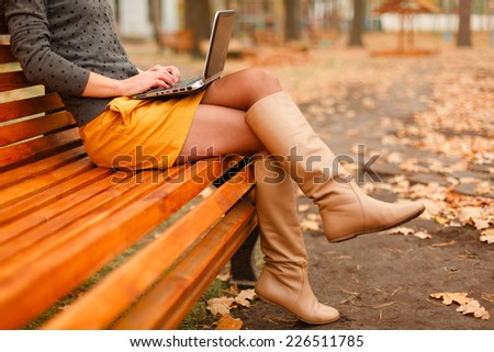 young woman using laptop in the autumn park - stock photo