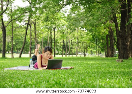 Young woman using laptop in the park - stock photo