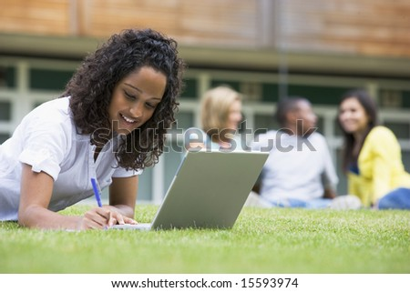 Young woman using laptop on campus lawn, with other students relaxing in background
