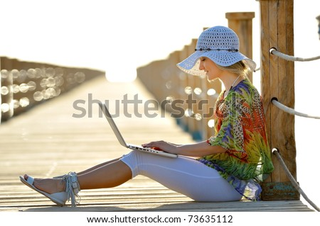 young woman using laptop outdoor in summer