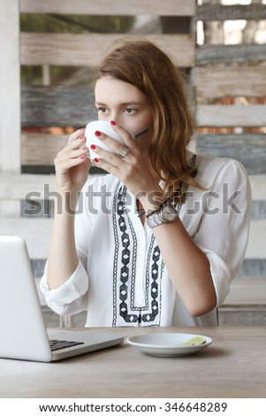 Young woman using laptop while drinking tea - stock photo