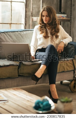 Young woman using laptop while sitting in loft apartment - stock photo