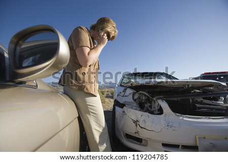 Young woman using mobile phone by car wreckage - stock photo