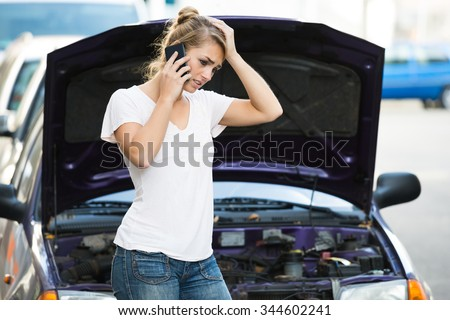 Young woman using mobile phone while looking at broken down car on street - stock photo