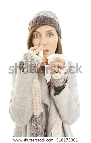 Young woman using nose drops isolated on white background. Portrait of a girl with a nasal spray and tissue in hands. The concept of treatment for allergies or the common cold. Winter style