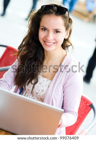 Young woman using notebook in cafe - stock photo