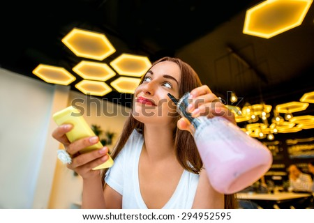 Young woman using phone and holding beaker with drink in modern interior lab or cafe - stock photo