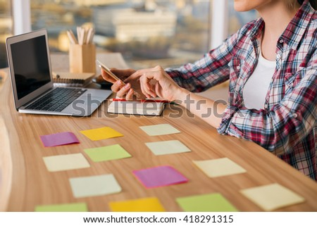 Young woman using phone at creative desktop with blank laptop screen and colorful stickers. Mock up - stock photo