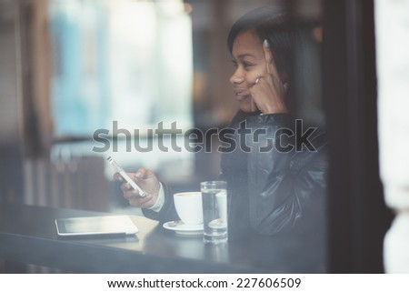 Young woman using phone in coffee shop - stock photo