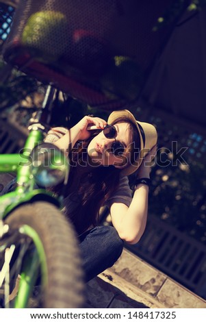 Young woman using phone next to her bicycle. - stock photo