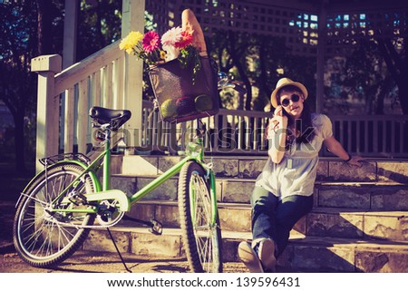 Young woman using phone next to her bicycle with fresh flowers and fruits in basket. - stock photo