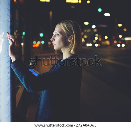 Young woman using self service digital screen for touristic information, attractive caucasian blonde female touching big terminal display and hold smart phone while standing in night city with lights - stock photo