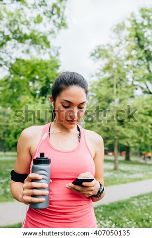 Young woman using smart phone after running - stock photo