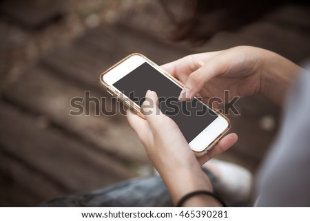 young woman using smart phone at Railroad tracks ,Vintage style photo.