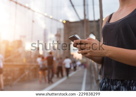 Young Woman Using Smart Phone on Brooklyn Bridge - stock photo