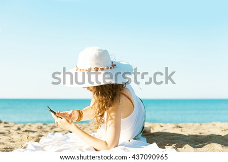 Young woman using smart phone on the beach