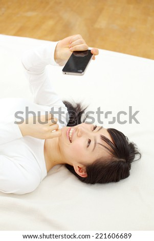 young woman using smart phone on the bed