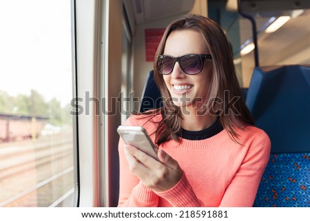 Young woman using smart phone while traveling by train - stock photo