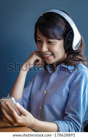Young woman using smartphone at work with wireless headphone