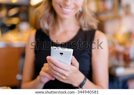 Young woman using smartphone indoors. Focus on hands.