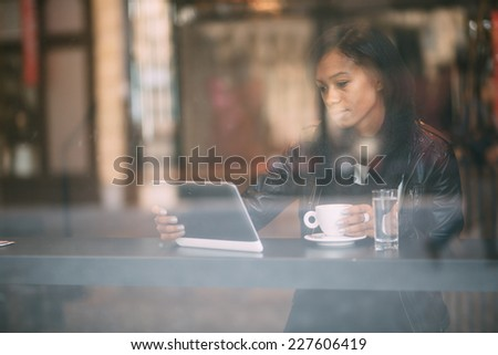 Young woman using tablet computer in coffee shop - stock photo
