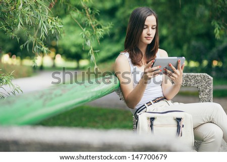 Young woman using tablet computer on a park bench - stock photo