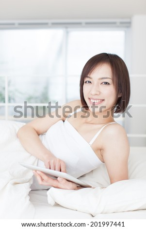 young woman using tablet computer on the bed - stock photo