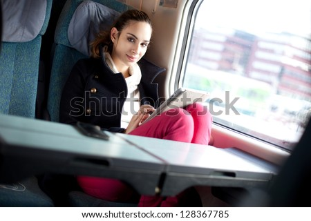 Young woman using tablet computer on the train - stock photo