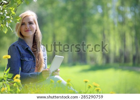 Young woman using tablet in spring park with flowers