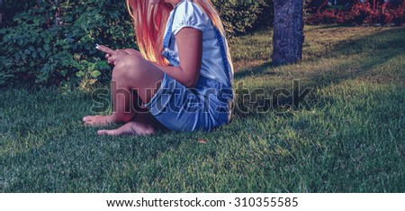 Young woman using tablet outdoor is sitting on grass, no face, side view. Copyspace. A lot of space for text - stock photo