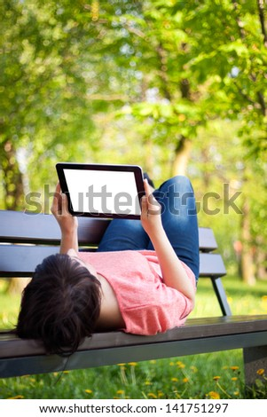 Young woman using tablet outdoor laying on grass