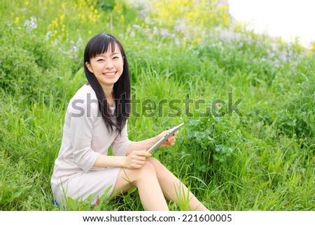 Young woman using tablet outdoor laying on grass, smiling. - stock photo