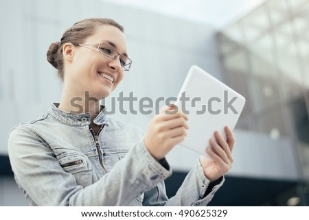 Young woman using tablet outdoors