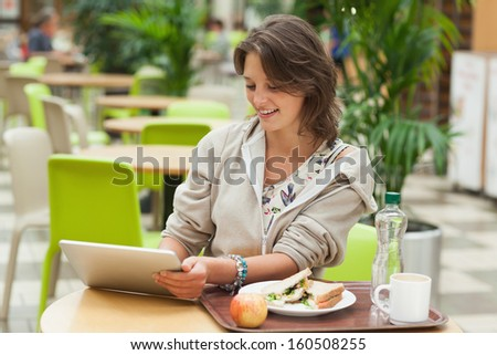 Young woman using tablet PC while having meal in the cafeteria