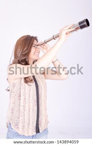 Young woman using telescope - stock photo