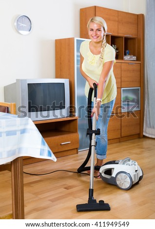 Young woman using vacuum cleaner during regular clean-up - stock photo