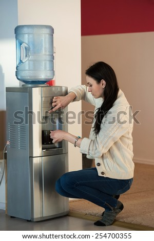 Young woman using water dispenser at office - stock photo