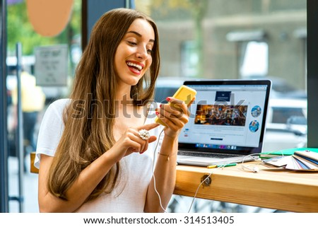 Young woman using yellow smart phone sitting near the window with laptop and colorful stuff on the table in the cafe - stock photo